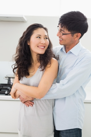 hugging couple: Smiling young man embracing woman from behind in the kitchen at home Stock Photo