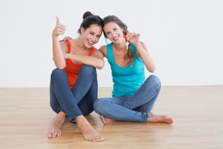Portrait of two cheerful female friends gesturing thumbs up with house keys sitting on the floor Stock Photo - 25481057