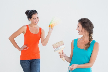 Two female friends with paint brush choosing color for painting a room in new house photo
