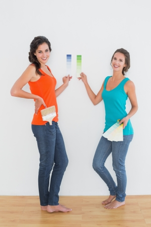 Side view portrait of two female friends choosing color in a new house photo