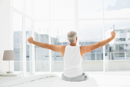 Rear view of a mature man waking up in bed and stretching his arms Фото со стока
