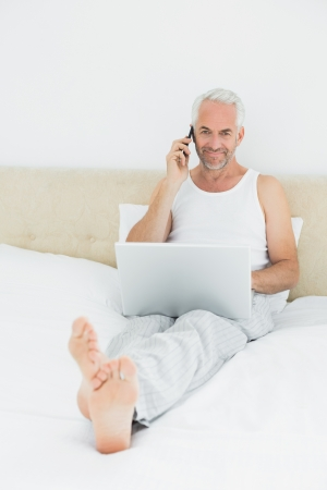 Portrait of a casual smiling mature man using cellphone and laptop in bed at home photo