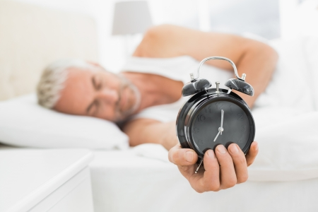 extending: Sleepy mature man holding out alarm clock in bed at home