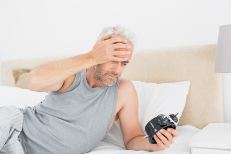 late 50s: Mature man looking at alarm clock in bed at home