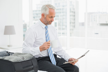 Mature businessman with coffee cup reading newspaper by luggage at a hotel room photo