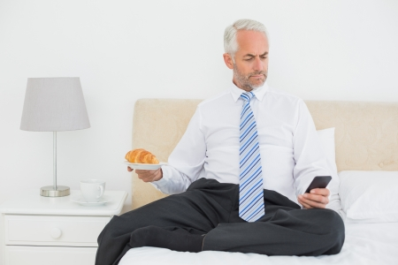 Serious well dressed man text messaging while holding croissant in bed at home photo