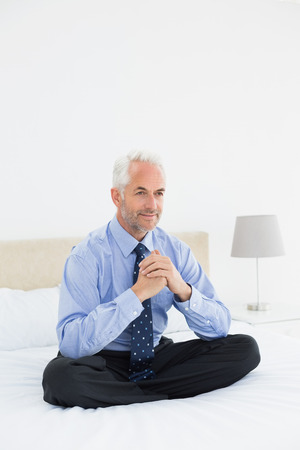 Full length of a relaxed smiling mature businessman sitting in bed at home photo