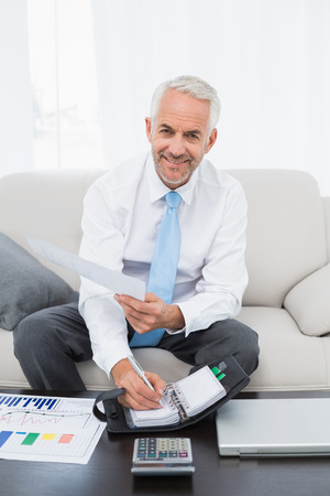 Smiling mature businessman with graphs and diary sitting in the living room at home Stock Photo