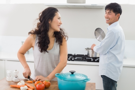 woman cooking: Young couple preparing food together in the kitchen at home