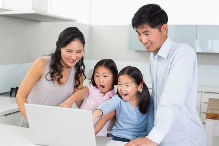 Happy shocked family of four using laptop in the kitchen at home photo