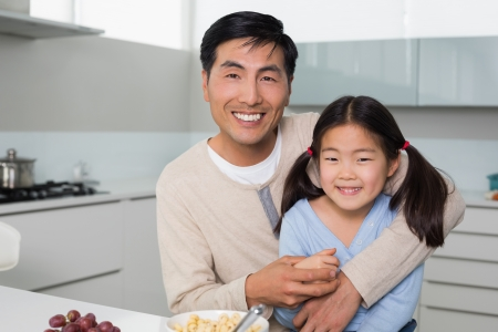 Portrait of a happy father with young daughter in the kitchen at home photo