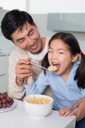 Cheerful father with young daughter having cereals in the kitchen at home photo