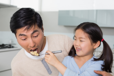 Close-up of a young daughter feeding cereals to father in the kitchen at home photo