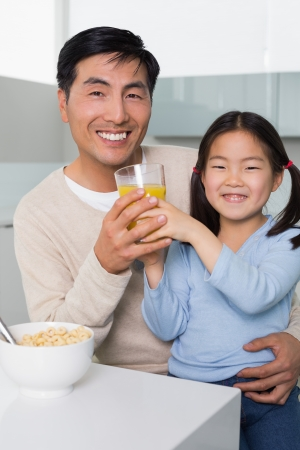 Portrait of a happy father with young daughter having breakfast in the kitchen at home photo