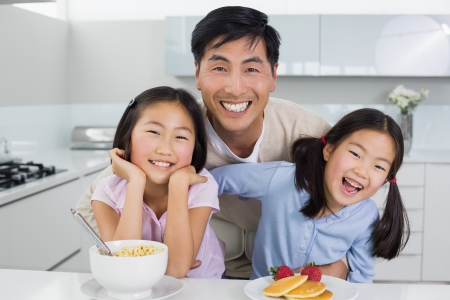 father and daughter: Retrato de un hombre sonriente con dos hijas felices de desayunar en la cocina en el hogar