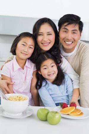comer sano: Retrato de una pareja sonriente con dos hijas felices de desayunar en la cocina en el hogar