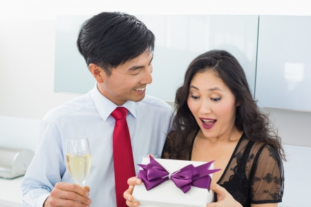 gifting: Shocked woman opening a gift box by man with champagne in the kitchen at home