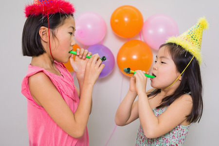 noisemaker: Side view of two young girls blowing noisemakers at a birthday party
