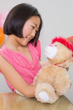 soft toy: Close-up of cute little girl with her soft toy at a birthday party Stock Photo
