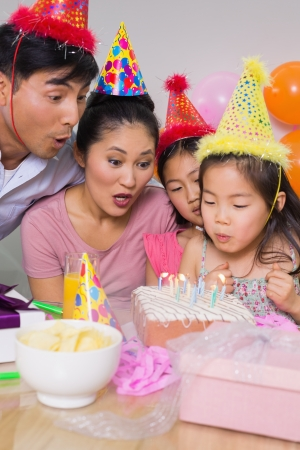 Family of four blowing cake at a birthday party photo