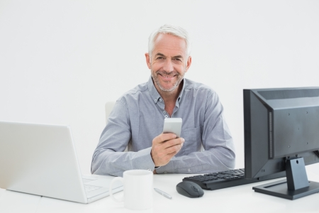 Portrait of a mature businessman with cellphone, laptop and computer at desk against white background photo