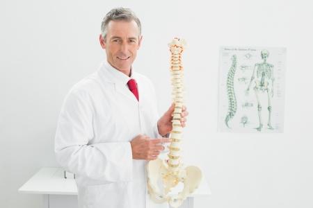 beenderige: Portret van een lachende mannelijke arts die skelet model in zijn kantoor