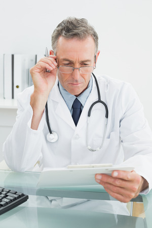 Serious male doctor reading a report at desk in medical office Stock Photo - 25498638