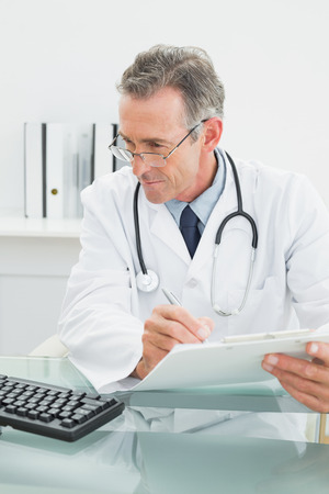 doctor computer: Concentrated male doctor writing a report at desk in medical office