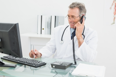 Smiling male doctor using computer and telephone at the medical office photo