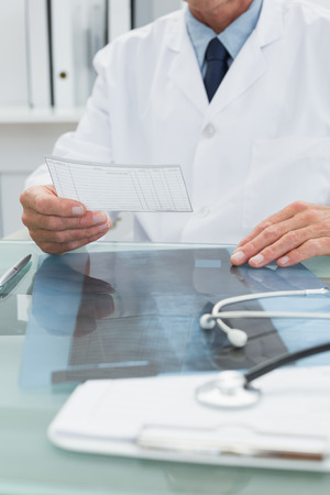 Mid section of a male doctor reading a note at desk in medical office photo