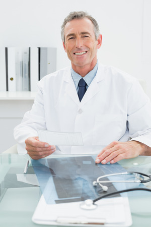 Portrait of a smiling male doctor sitting at desk in medical office photo