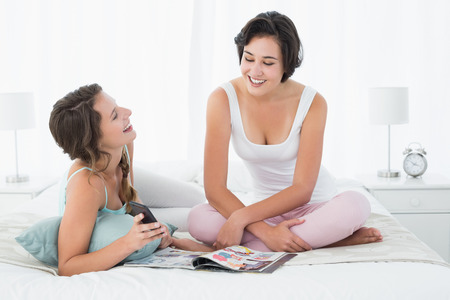 Relaxed smiling young female friends with magazine chatting in bed at home photo