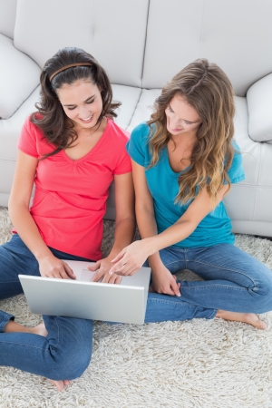 High angle view of two smiling young female friends using laptop in the living room at home photo