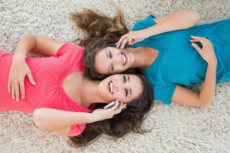 pijamada: Vista de ángulo alto de dos jóvenes amigos femenina acostado en la alfombra y el uso de teléfono móvil en la sala de estar en casa