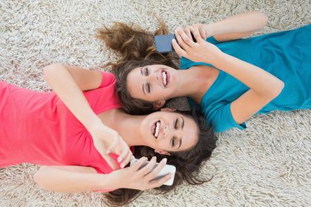 pijamada: Vista de ángulo alto de dos jóvenes amigas que mienten en la alfombra y la mensajería de texto en el salón de su casa