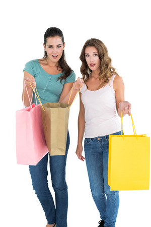 Portrait of two happy young female friends with shopping bags over white background photo
