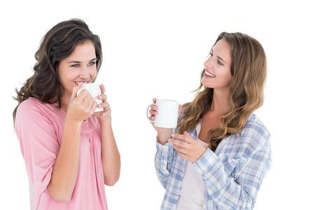 mujer tomando cafe: Dos jóvenes amigas sonriente beber café sobre fondo blanco
