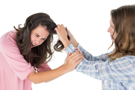 Side view of an angry young woman pulling females hair in a fight over white background photo