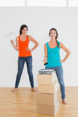 Full length portrait of two female friends with paint brushes in a new house photo