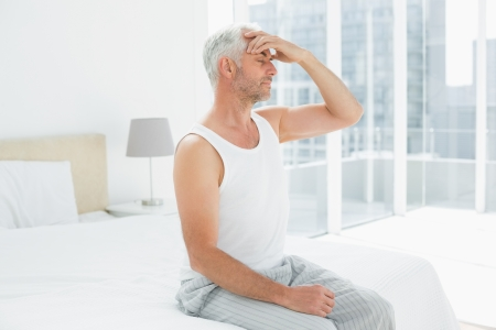 pounding head: Side view of a mature man suffering from headache in bed at home Stock Photo
