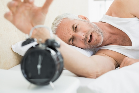 extending: Sleepy mature man extending hand to alarm clock in bed at home