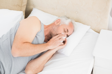 High angle view of a mature man suffering from cold as he lie in bed at home photo
