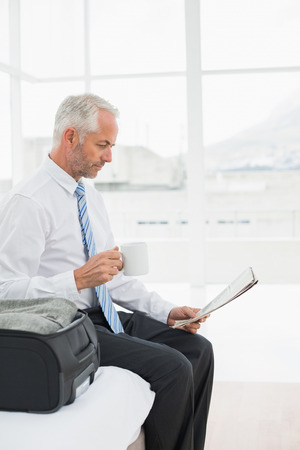 Side view of a mature businessman with coffee cup reading newspaper by luggage at a hotel room photo