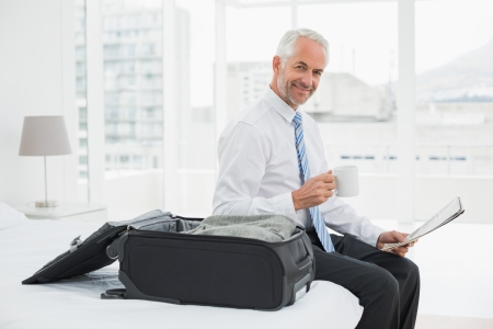 Side view portrait of a mature businessman with coffee cup reading newspaper by luggage at a hotel room photo