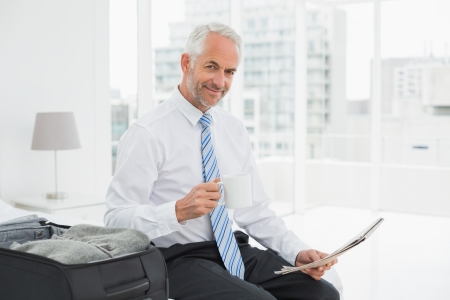 well read: Portrait of a mature businessman with coffee cup reading newspaper by luggage at a hotel room
