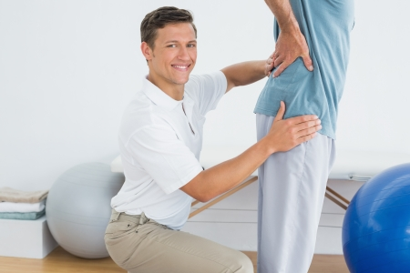 Side view portrait of a male therapist massaging mans lower back in the gym at hospital photo