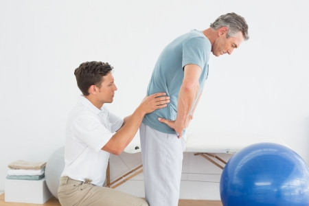 Side view of a male therapist massaging mans lower back in the gym at hospital photo
