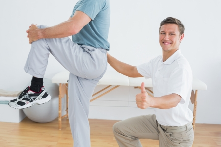 Side view portrait of a male therapist massaging mans lower back while gesturing thumbs up in the gym at hospital photo
