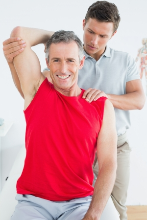 Male physiotherapist stretching a smiling mature mans arm in the hospital