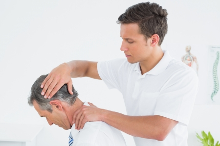 Side view of a male chiropractor doing neck adjustment